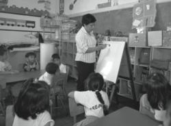 Maestra con estudiantes y rotafolios.png