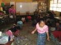 Salón de clases con maestra y estudiantes indígenas.png